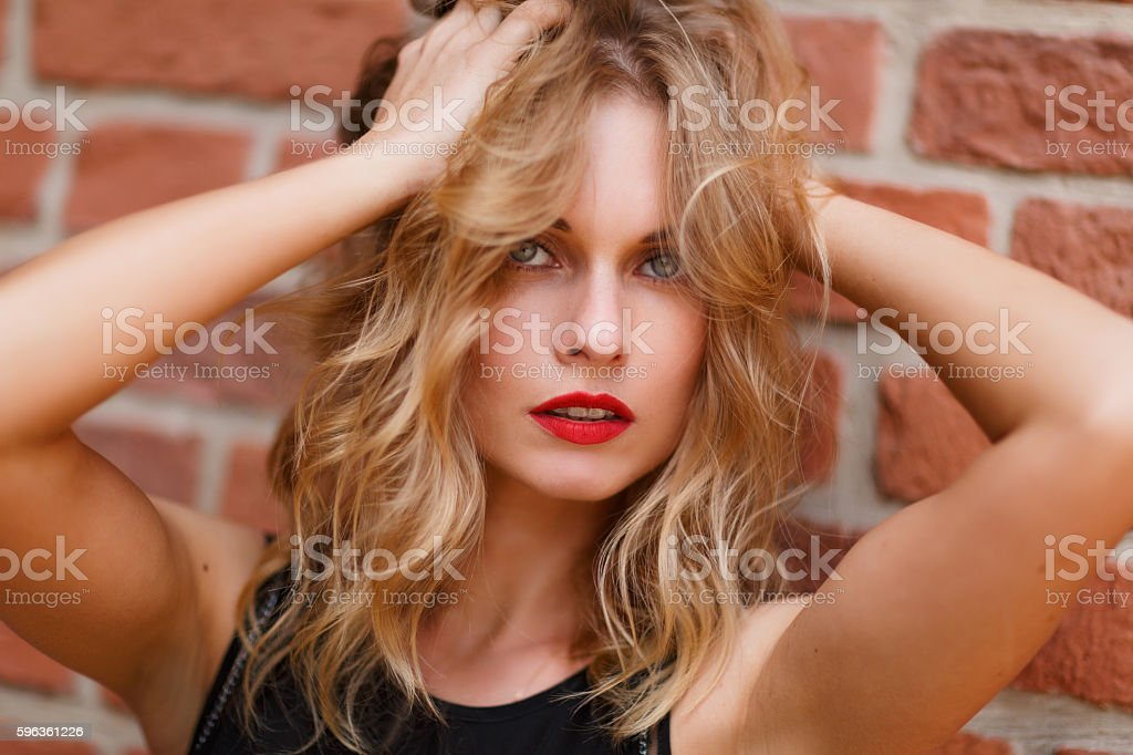 Attractive young blonde woman with red lips touching her hair royalty-free stock photo
