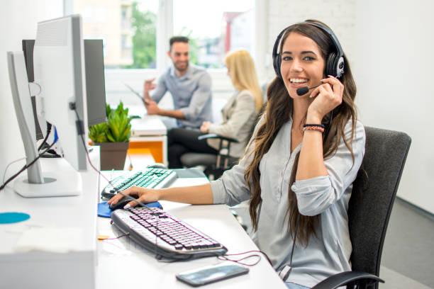 Attraktive junge Geschäftsfrau mit Headset, die im Call Center arbeitet. – Foto