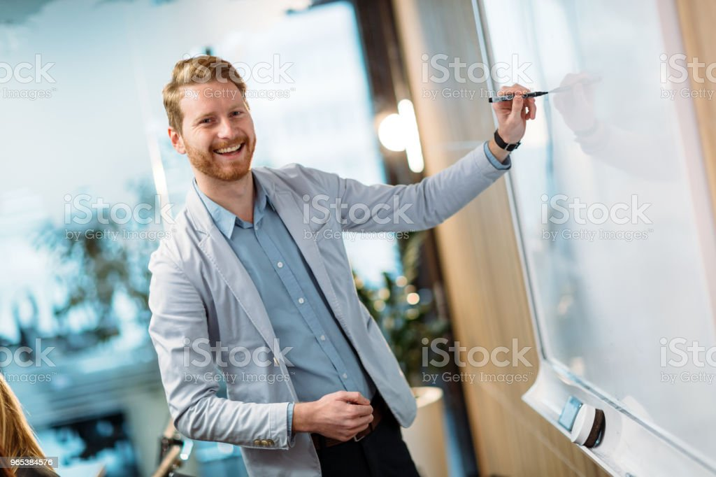 Attractive young businessman doing presentation in office zbiór zdjęć royalty-free