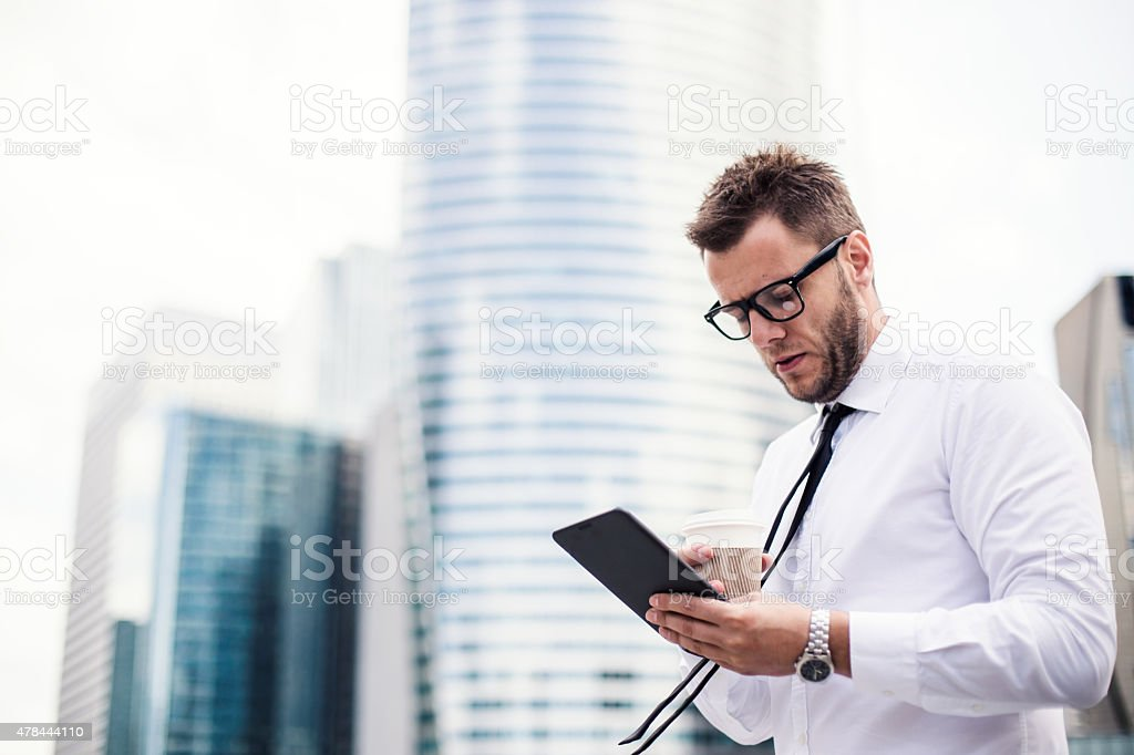 Attractive young businessman using a tablet and drinking coffee. stock photo