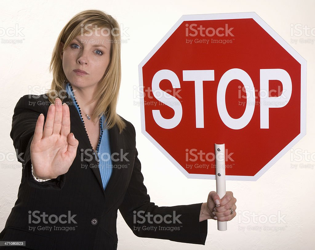 Attractive young businesswoman holds up 'Stop' sign royalty-free stock photo