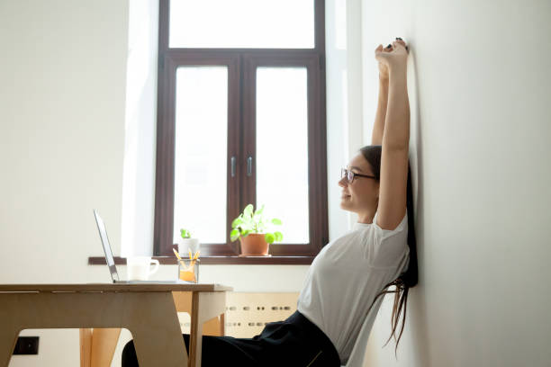 attractive young businesswoman relaxing, stretching at desk in home office - poprawna postawa zdjęcia i obrazy z banku zdjęć