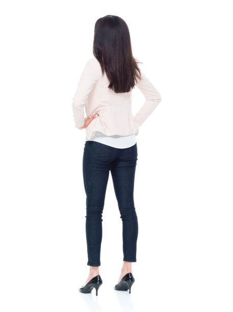 attractive young businesswoman with hands on hips - rear view stock photos and pictures