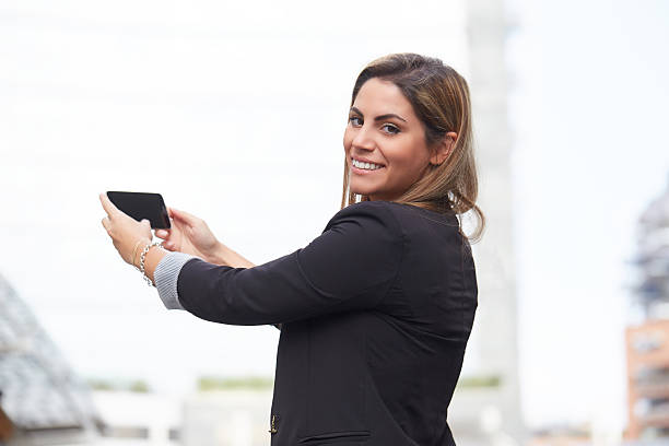 Attractive young businesswoman with tablet take selfie stock photo