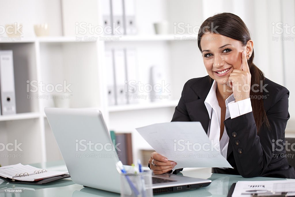 Attractive young businesswoman working on documents in office stock photo