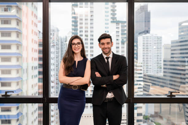 Attractive young caucasian business partner standing crossed arm with smiling and looking at camera in modern office stock photo