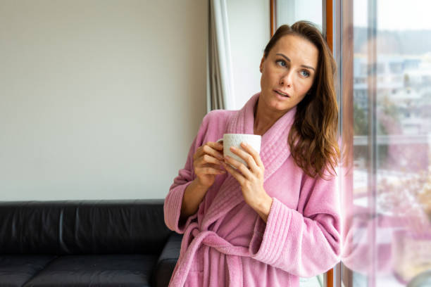 Attractive young caucasian woman alone in home apartment, in romantic thoughts, leaning against a bright-lit terrace window in her living room stock photo