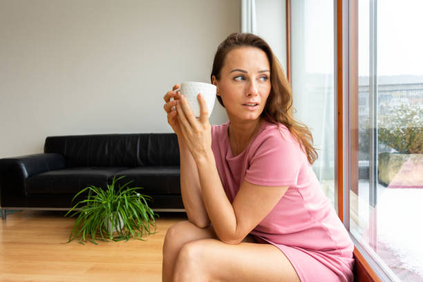 Attractive young caucasian woman alone in home apartment, remembering her day with a cup of tea in the afternoon stock photo