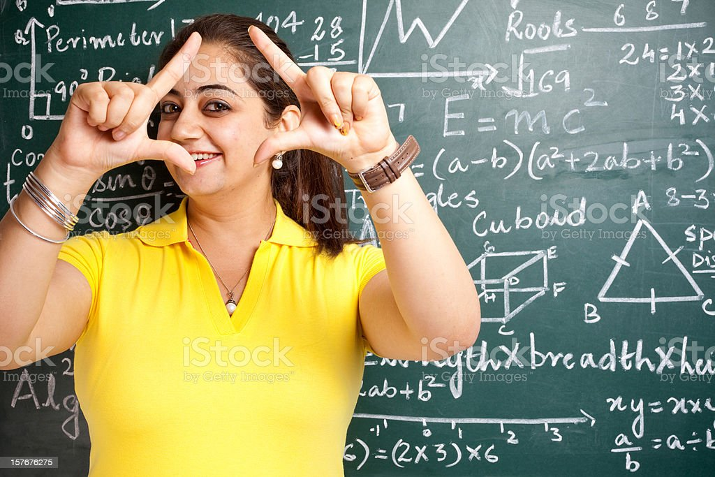 Attractive Young Cheerful Indian Mathematics Girl Teacher Classroom with Greenboard stock photo