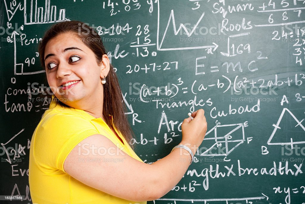 Attractive Young Cheerful Indian Mathematics Teacher in Classroom with Greenboard stock photo