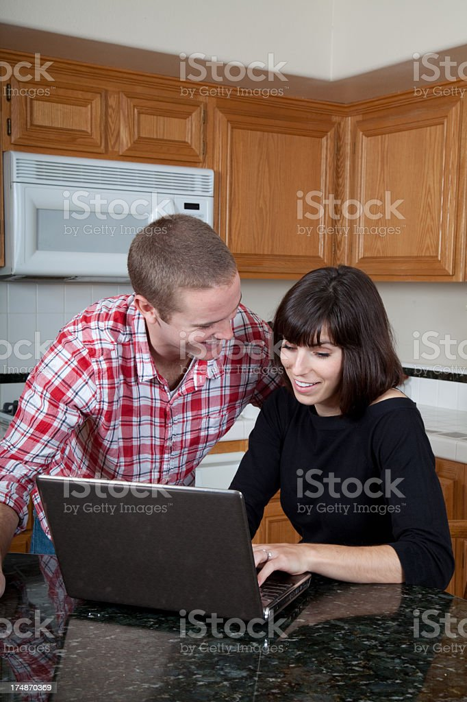 Attractive young couple at the computer royalty-free stock photo