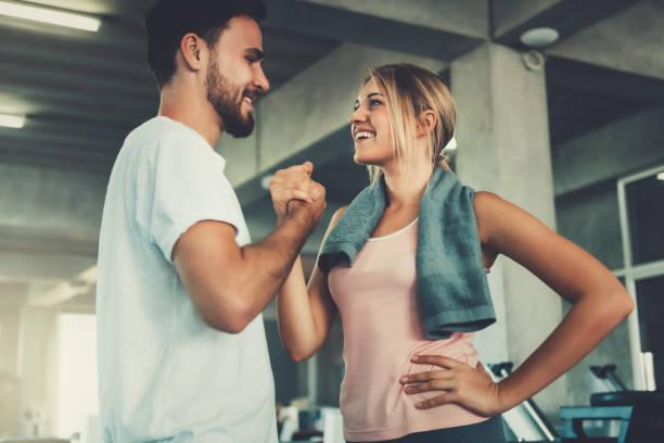 在健身房鍛煉後, 有吸引力的年輕夫婦握手....... 夫妻倆的愛情肖像是一起鍛煉的。 - 肌肉發達 個照片及圖片檔