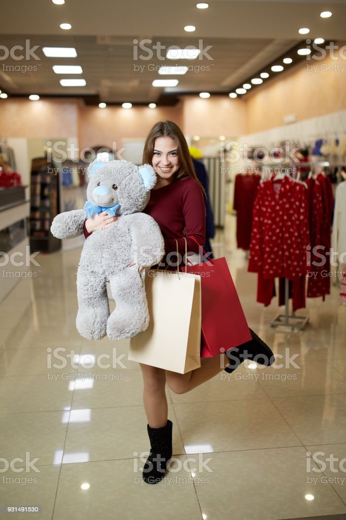 Attractive young cute caucasian woman hugs plush teddy bear with shopping bags at clothing store front. Pretty girl shopper happy with her purchases and prize in shop sale competition stock photo