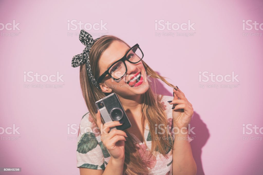 Attractive young cute girl posing with old retro film camera. stock photo