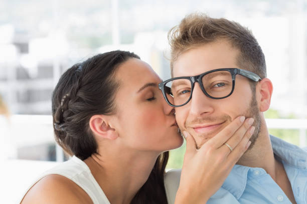 attractive young designer getting a kiss from a co worker - brunette woman eyeglasses kiss man foto e immagini stock