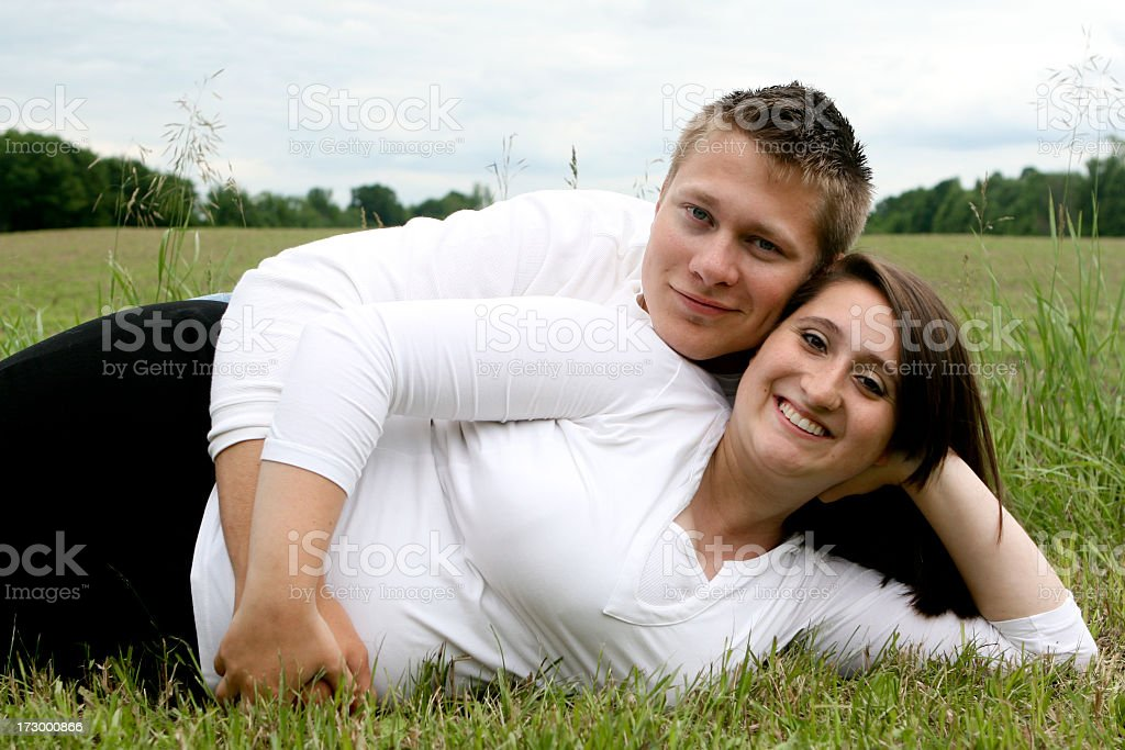 Attractive young expecting couple lying next to field stock photo
