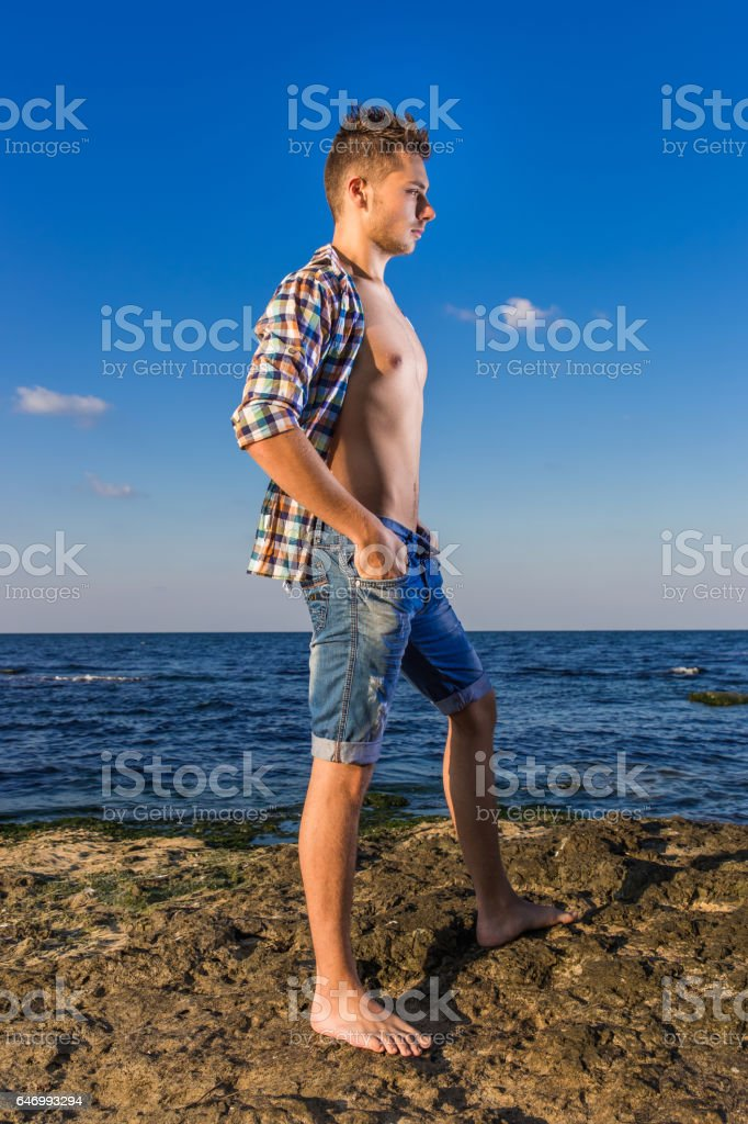 Attractive young fashion sexy man on rock near the sea water stock photo