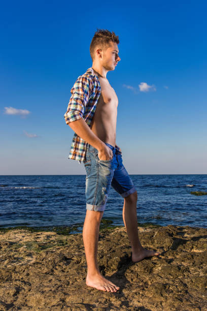 attractive young fashion sexy man on rock near the sea water - young nudist boys stock photos and pictures