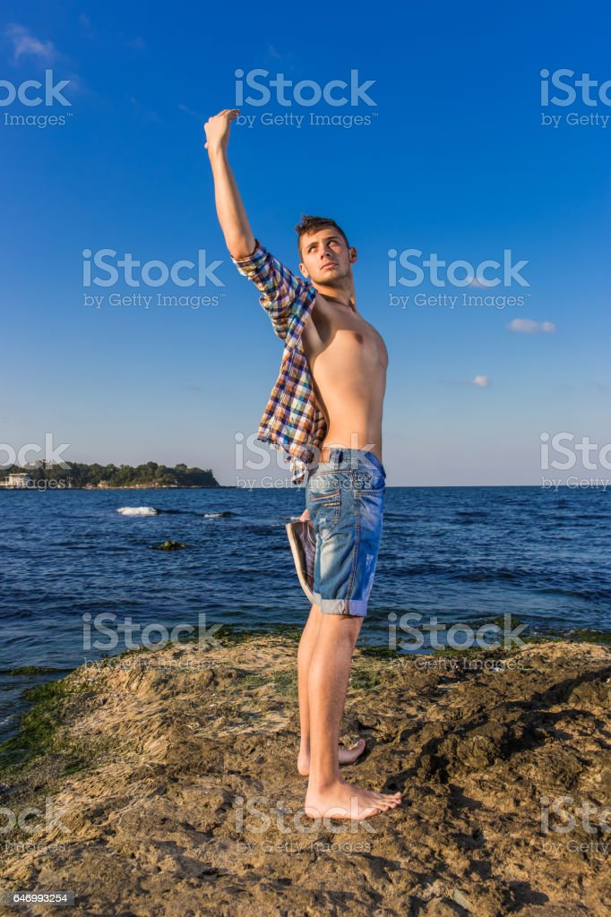 Attractive young fashion sexy man on rock near the sea water with shoes in hand stock photo