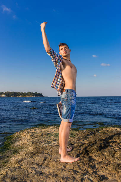 attractive young fashion sexy man on rock near the sea water with shoes in hand - young nudist boys stock photos and pictures