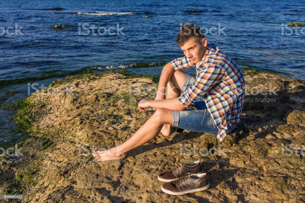 Attractive young fashion sexy man sitting on a rock near the sea water with shoes beside him stock photo