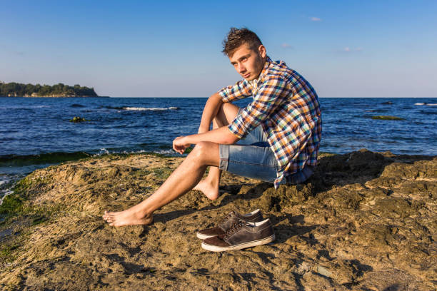 attractive young fashion sexy man sitting on a rock near the sea water with shoes beside him - young nudist boys stock photos and pictures