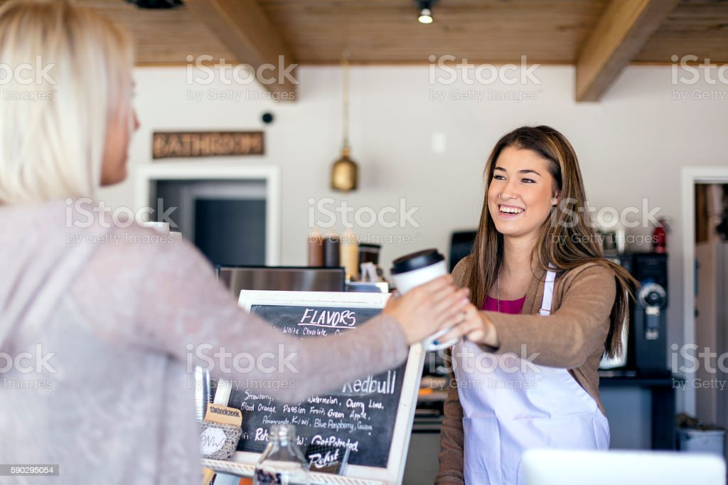 Attractive young female barista handing coffee to a customer royaltyfri bildbanksbilder