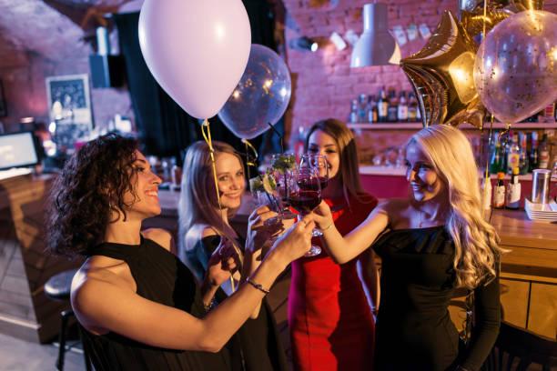 Intéressante de jeunes amis femmes célébrant un standing vacances avec verres de vin en bar branché - Photo
