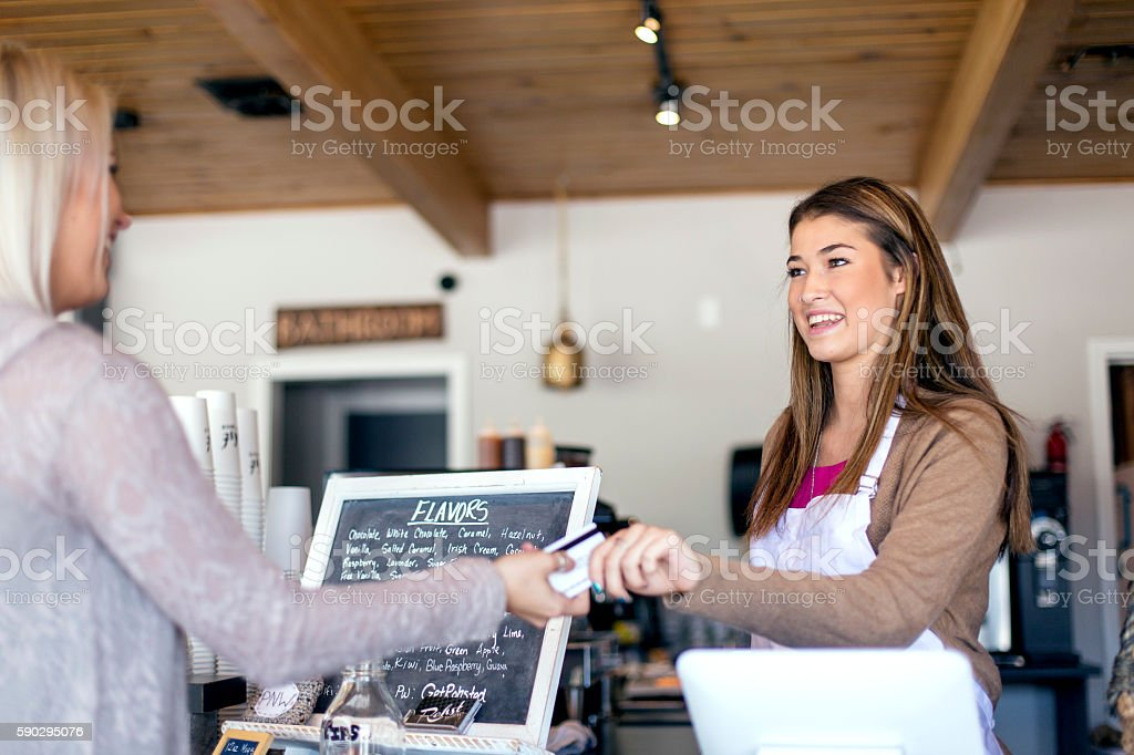 Attractive young female handing a payment card to a customer royaltyfri bildbanksbilder