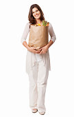 Full length portrait of a attractive young female holding a bag of fresh healthy groceries. Vertical shot. Isolated on white.