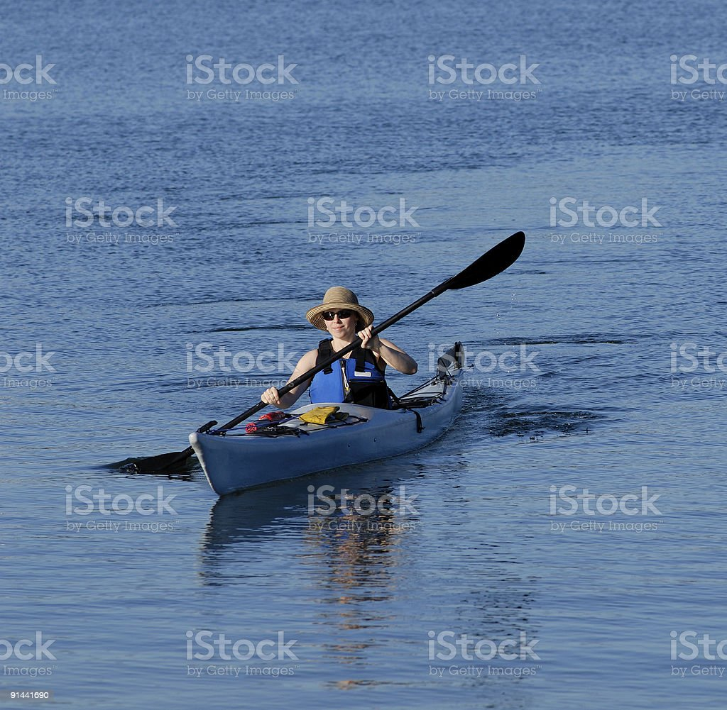 Attractive young female kayaker rowing royalty-free stock photo