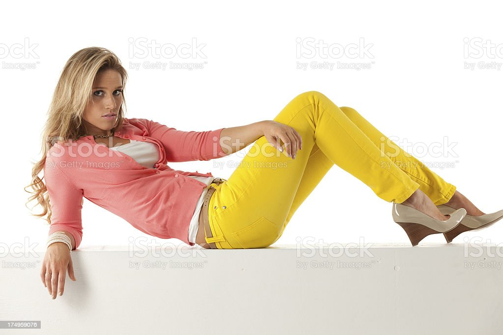 Attractive young female lying on a ledge stock photo