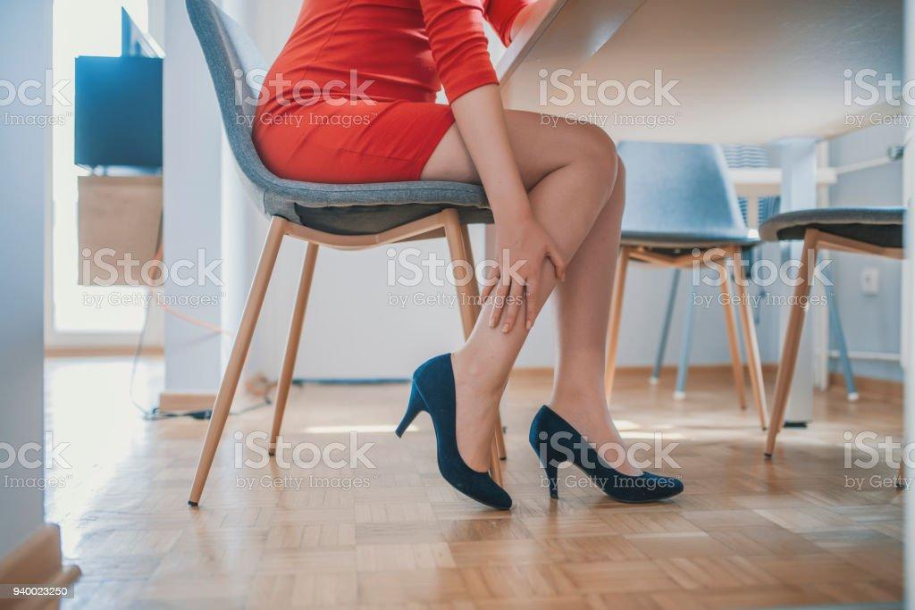 Empleado de oficina femenino joven atractivo terminado el trabajo volver a sentarse y relajarse y pies sensación dolorosas sacar zapatos del alto talón con masaje de la mano - foto de stock