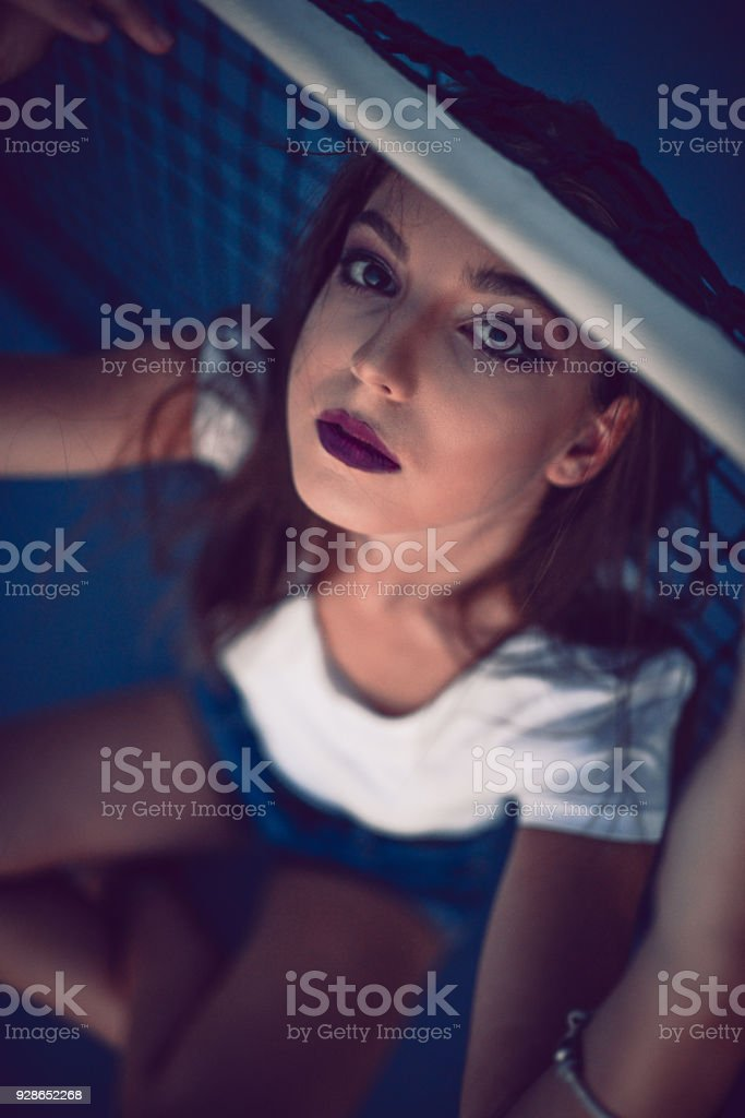Attractive Young Female Posing at Tennis Court on the Net stock photo