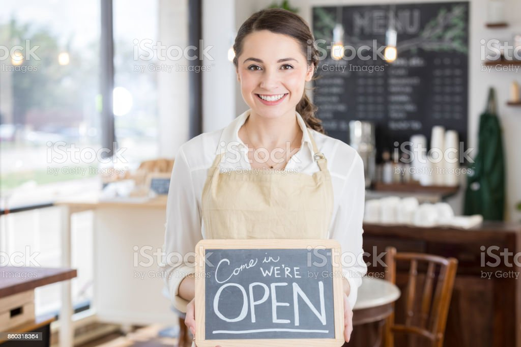 Attractive young female restaurant owner with 'Open' sign stock photo