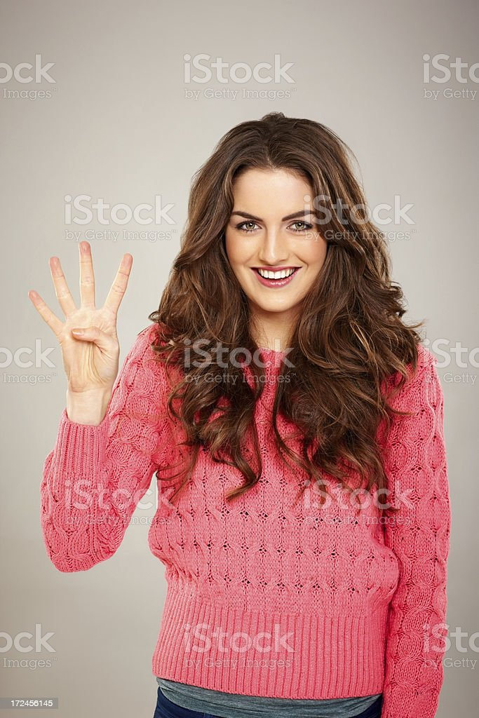 Attractive young female showing four fingers royalty-free stock photo