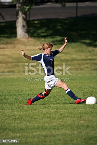 Soccer player strietches to control ball