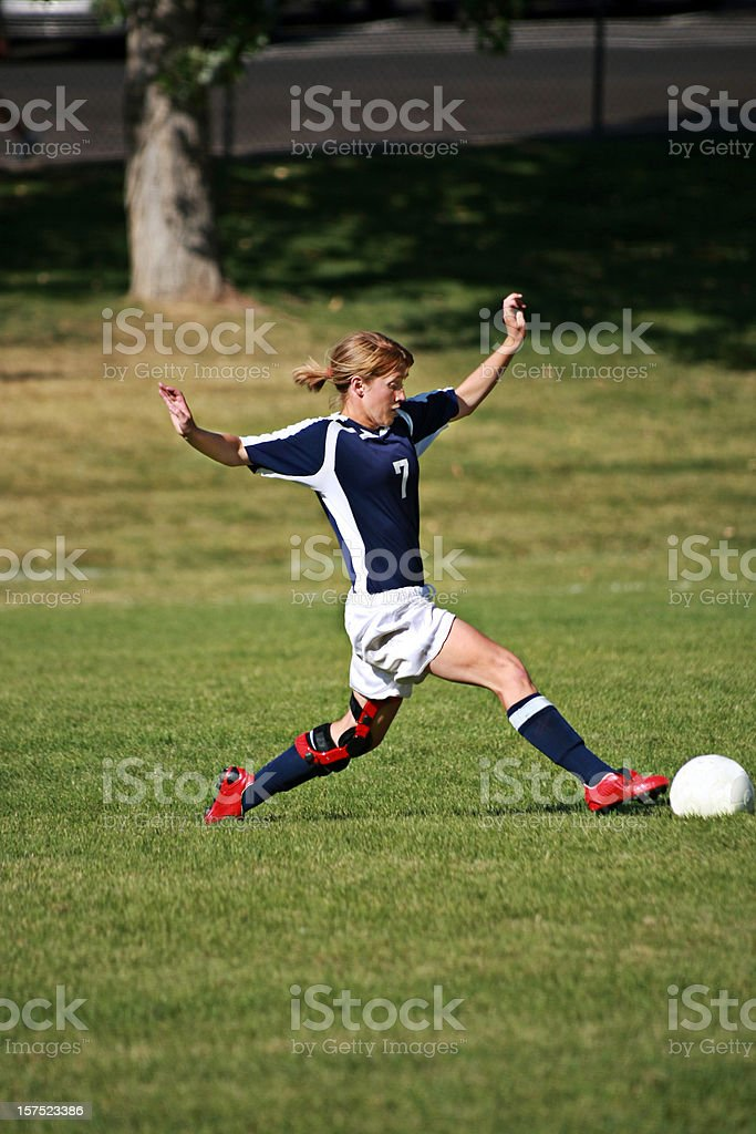 Attractive Young Female Soccer Player Stretches to Touch Ball stock photo