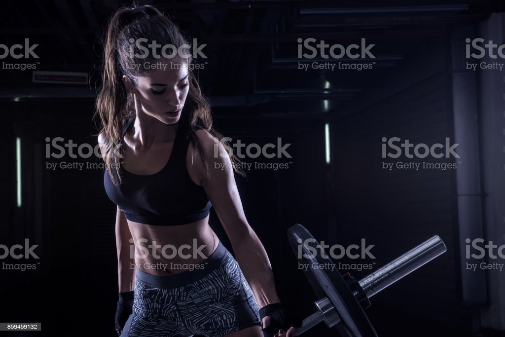 Attractive young fit sportswoman working out in training gym lifting stock photo
