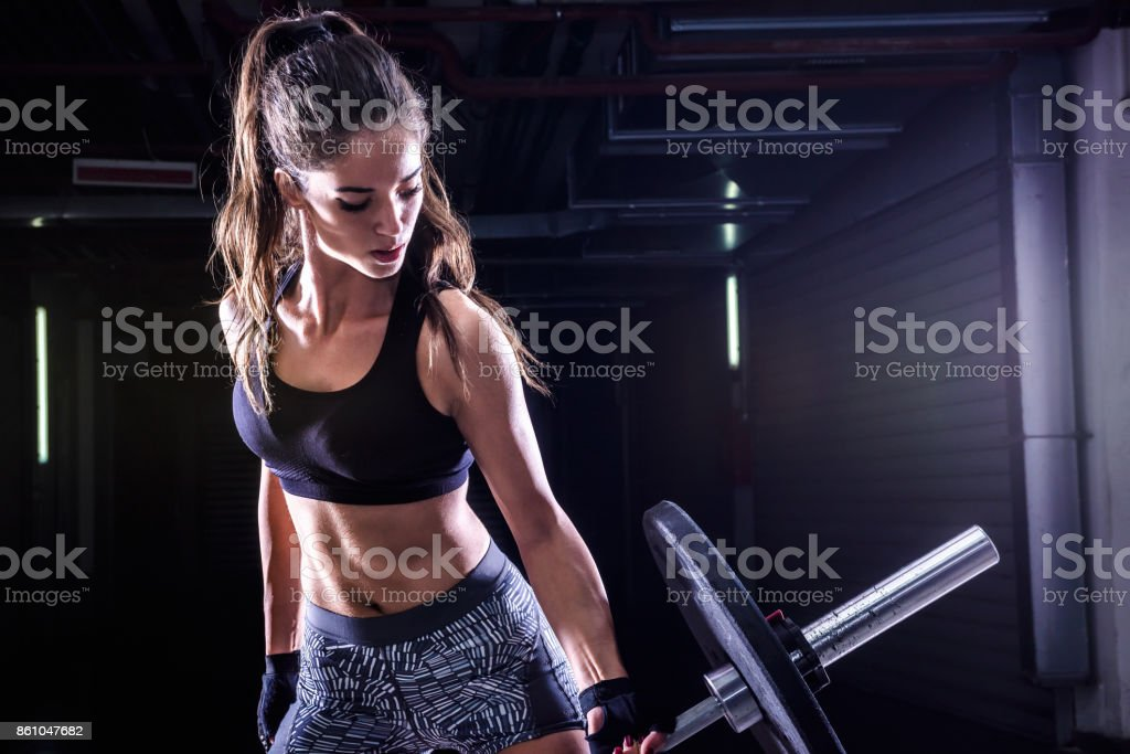 Attractive young fit sportswoman working out with weights stock photo