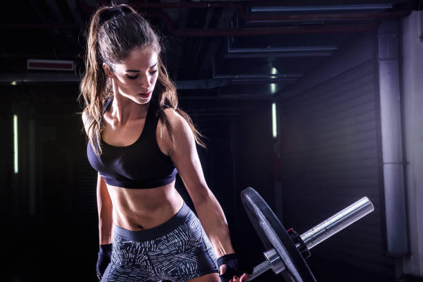 attractive young fit sportswoman working out with weights - woman muscular stock photos and pictures