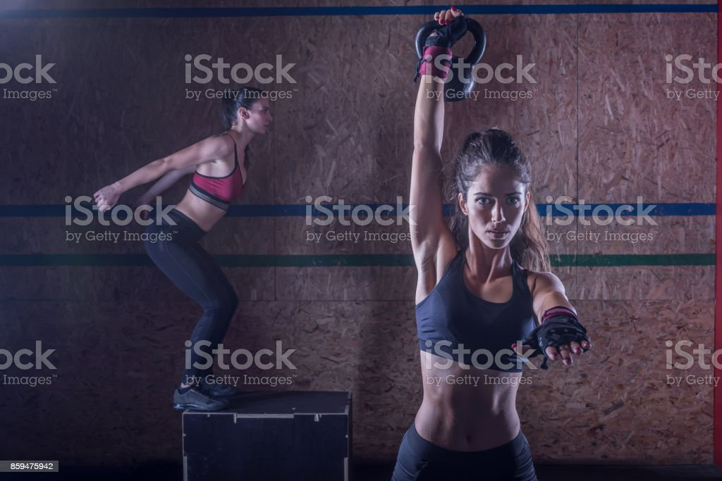 Attractive young fit sportswomen working out in training gym stock photo
