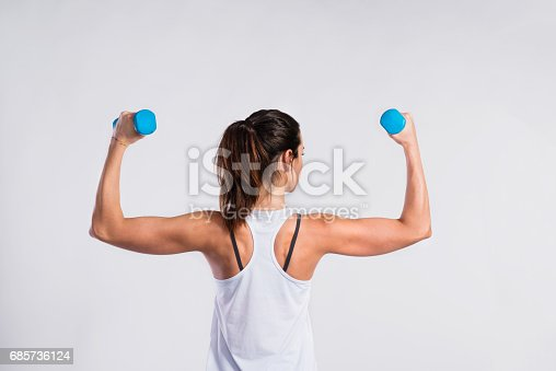istock Attractive young fitness woman holding dumbells. Studio shot. 685736124