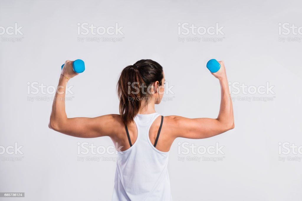 Attractive young fitness woman holding dumbells. Studio shot. stock photo