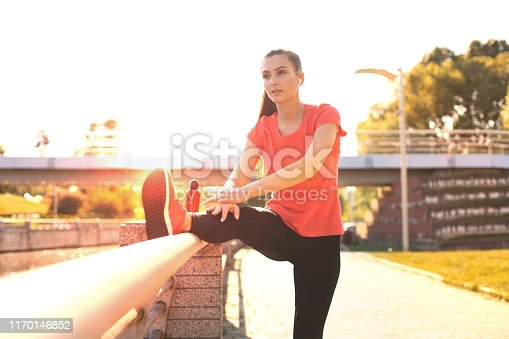 istock Attractive young fitness woman wearing sports clothing exercising outdoors, stretching exercises. 1170146852