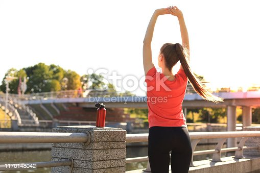 istock Attractive young fitness woman wearing sports clothing exercising outdoors, stretching exercises. 1170148042