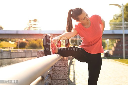 istock Attractive young fitness woman wearing sports clothing exercising outdoors, stretching exercises. 1170148891
