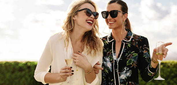 Attractive young friends with wine laughing Attractive young friends with wine laughing outdoors. Two stylish women having a great time together. high society stock pictures, royalty-free photos & images