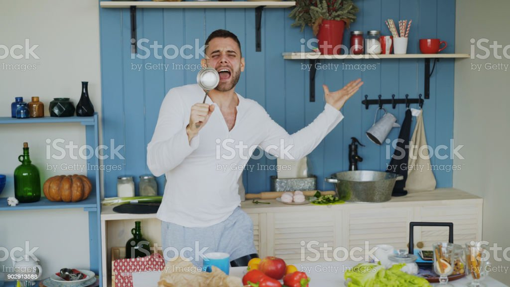 Attractive young funny man dancing and singing with ladle while cooking in the kitchen at home stock photo