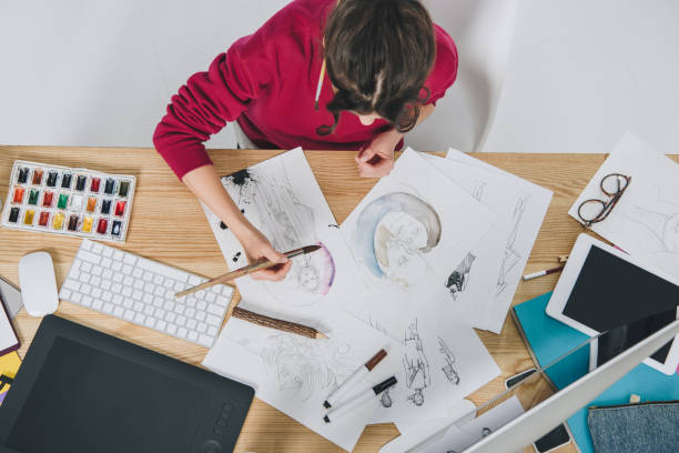 Attractive young girl drawing by table with computer Attractive young girl drawing by table with computer illustrator stock pictures, royalty-free photos & images